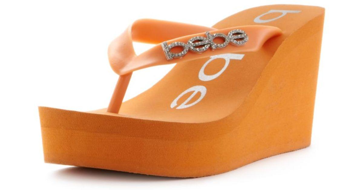 Bebe Kristy Wedge Flip Flop Sandals in Orange | Lyst