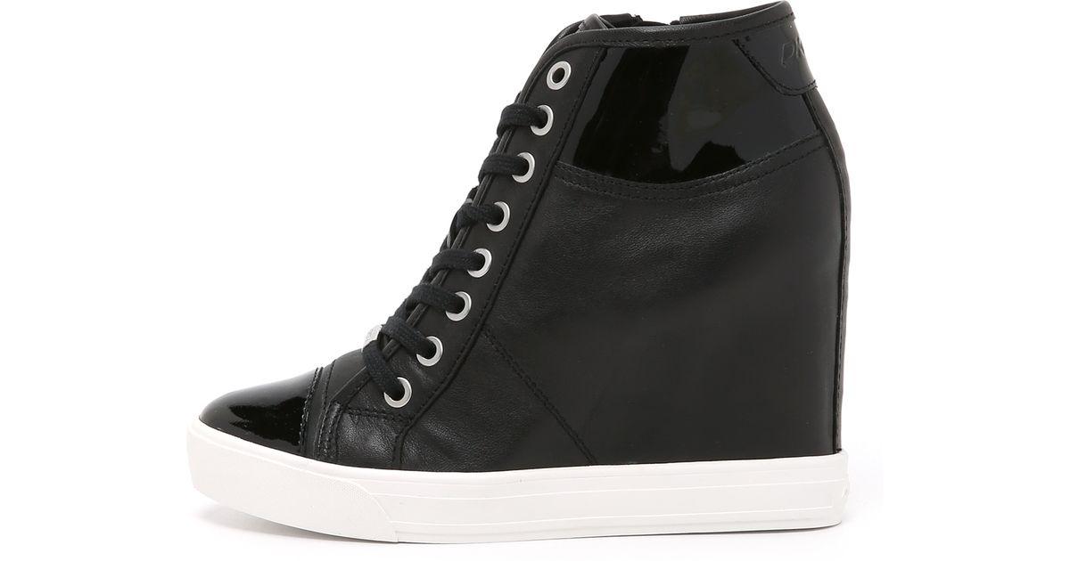 bbe75799958f Lyst - DKNY Grommet Zip Wedge Sneakers in Black