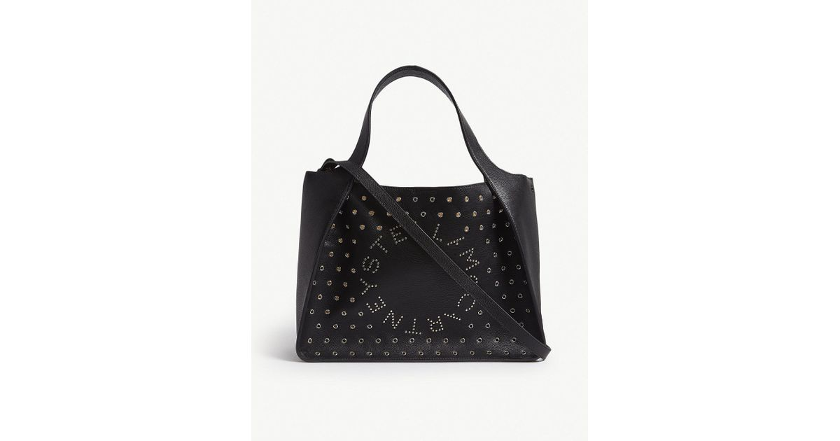 d2afd6a862b5 Lyst - Stella McCartney Black Eyelet Embellished Logo Faux Leather Tote Bag  in Black