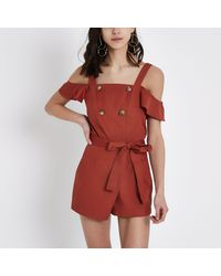 d44e4880129 River Island Rust Bardot Button Playsuit in Red - Lyst