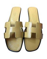 e25fda9eac58 Lyst - Hermès Oran Leather Mules in Yellow