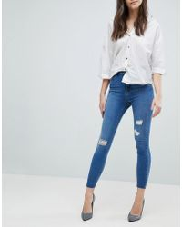 ASOS - Design Ridley High Waist Skinny Jeans In Pretty Mid Wash With Rip And Repair And Reverse Stepped Hem - Lyst