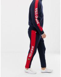 Polo Ralph Lauren Pantalon de survêtement à ourlet zippé avec bande à logo sur le côté - Bleu marine/rouge