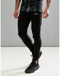 Muscle Monkey - Skinny Joggers In Black With Reflective Logo - Lyst 7ffdc5eea5950