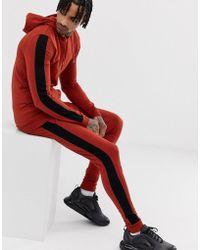 ASOS Rostfarbener Trainingsanzug bestehd aus Muskel-Kapuzenpullover mit extrem enger Jogginghose mit Seitenstreifen - Orange
