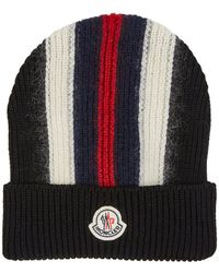 cd51f8f44ce646 Moncler's black rib-knit wool-blend beanie is detailed with navy, red, and  cream stripes. Crafted in Italy, this cap is finished a ... More