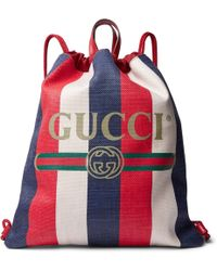 f9e33e59cf61 Gucci - Leather-trimmed Logo-print Striped Canvas Drawstring Backpack - Lyst