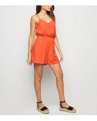31beffec88 Bardot Tiered Frill Romper. £46. River Island · New Look - Bright Orange  Strappy Button Front Playsuit - Lyst