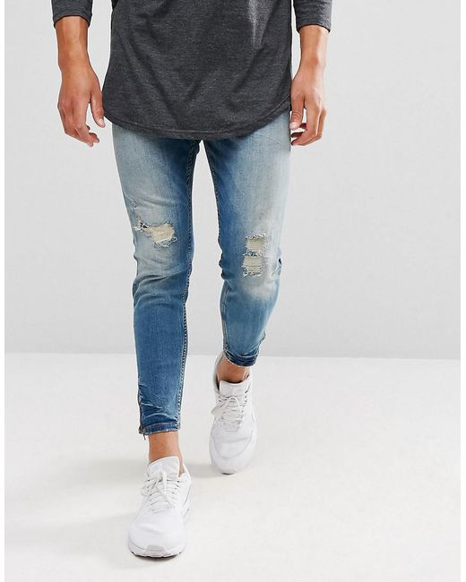 pull bear carrot fit ripped jeans with zipped hem in mid wash in blue for men lyst. Black Bedroom Furniture Sets. Home Design Ideas