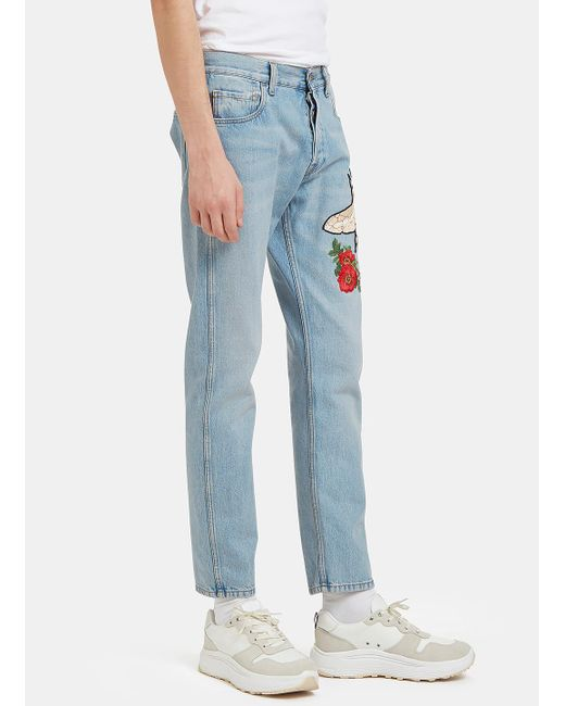 Gucci men s embroidered floral fly patch jeans in blue