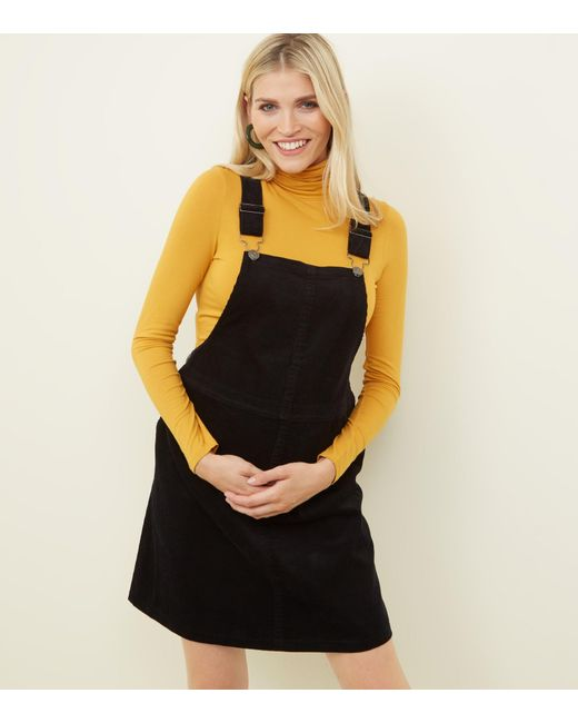 51b5d0806ce New Look Maternity Black Front Pocket Buckle Pinafore Dress in Black ...