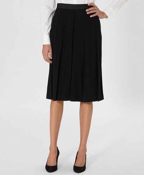 Wool Midi A-Line Skirt: Wool skirt with a slight A-line silhouette and a modern front inverted pleat that adds a unique touch. Front and back darts create a great shape. Front .