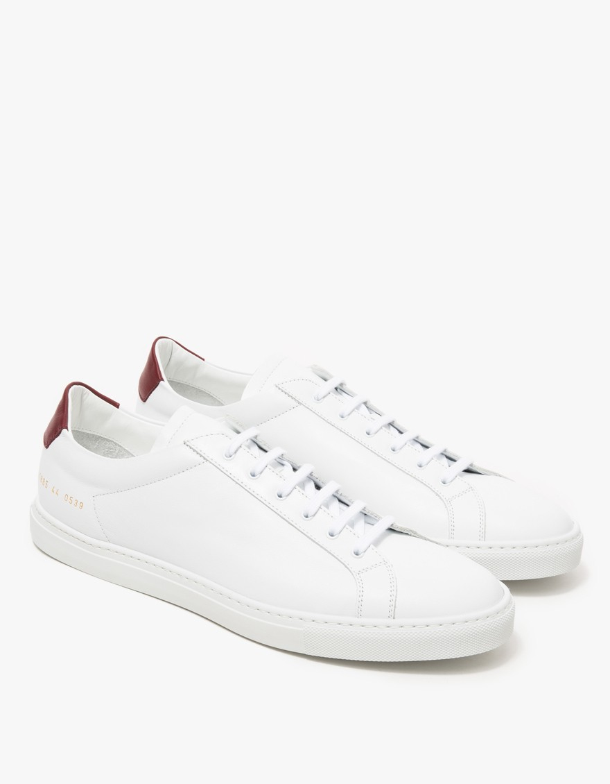 common projects achilles low white Common projects is a collaboration between designers flavio girolami and prathan poopat inspired by the lines and shapes of everyday objects, they design their.