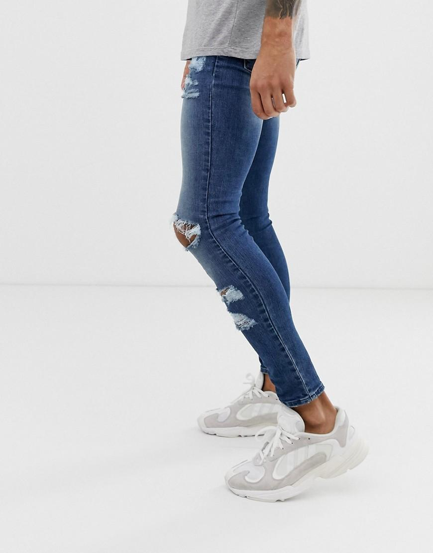 5b5e92ad Lyst - ASOS Spray On Jeans In Power Stretch With Heavy Rips In Mid Wash  Blue in Blue for Men
