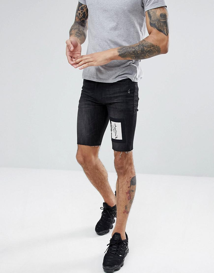 Religion. Short skinny en jean avec cusson squelette homme de coloris noir 7c7b9868aea