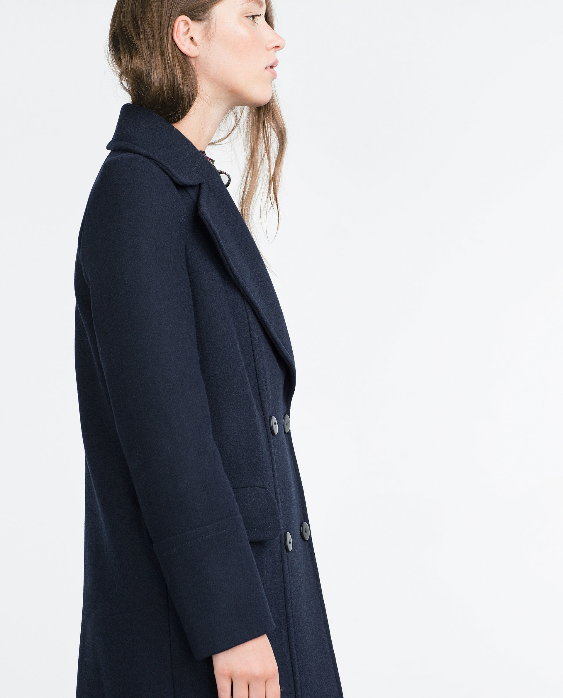 This stunning long wool coat for womens is beautifully fitted and tailored for a classic, feminine design. It features navy blue, a slim fitting bodice with elongated sleeves and tapered waist band leading into a long, flowing skirt, shoulders and sleeve cuffs have a pretty ruffle detailing.