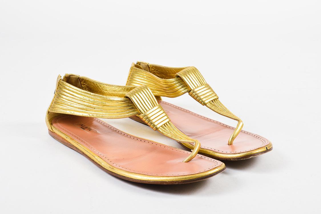 b1ec15244e595 Lyst - Alaïa Gold Metallic Leather Ribbed Strap Flat Thong Sandals ...