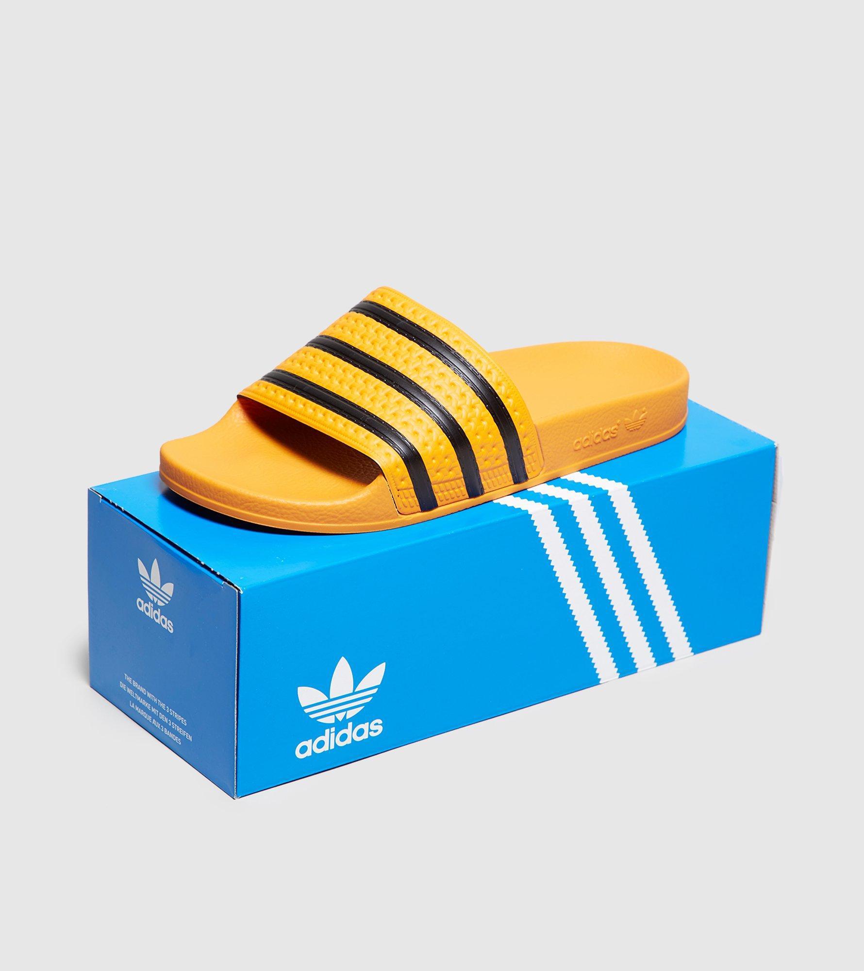 on sale 8f9f7 594b7 Lyst - Adidas Originals Adilette Slides in Orange