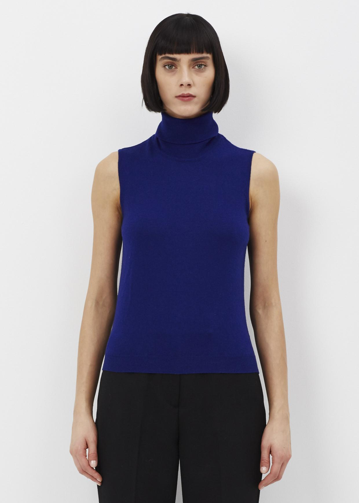 Prada's sleeveless turtleneck sweater is composed of beige, light blue, and yellow rib-knit virgin wool showcasing a zigzag and diamond pattern. Part of Runway Look 27, this sporty style is intarsia-knit at the front with a multicolored logo stripe.